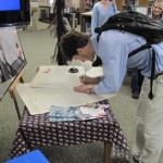 student signing at table