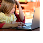 child held by woman at computer