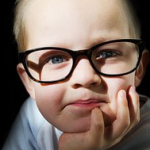 a little boy wearing eye glasses