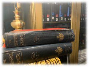 This is a photo of two leather bound volumes on top of each other with a light colored wooden bookshelf in the background